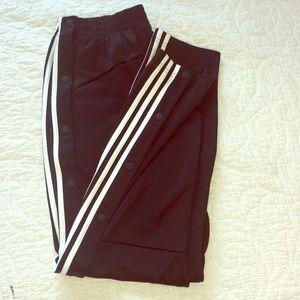 Black Adidas tear-away track pants.